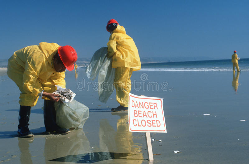 Workers cleaning up oil spill on beach. Hazardous material workers cleaning up oil spill, Huntington Beach, CA stock photo