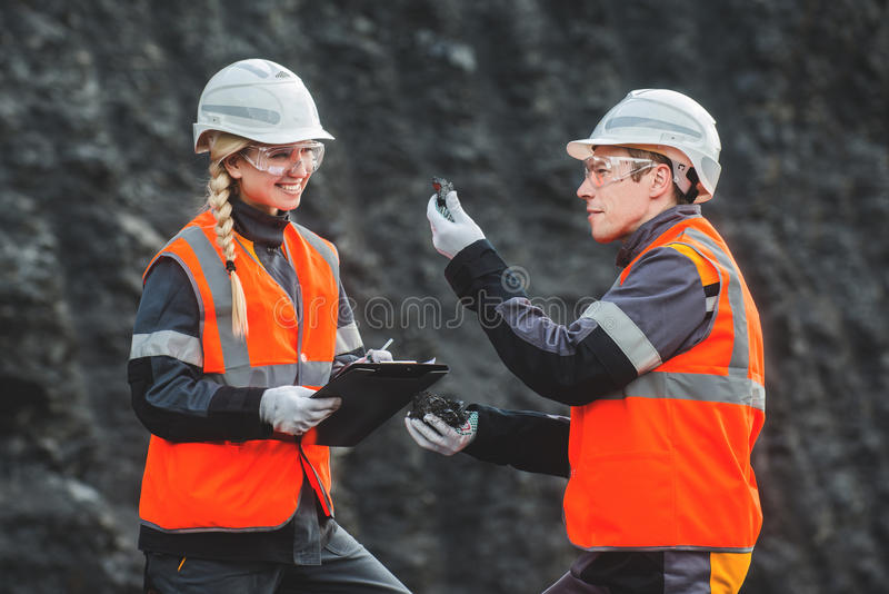 Workers with coal at open pit. Two speacialists examining coal at an open pit royalty free stock images
