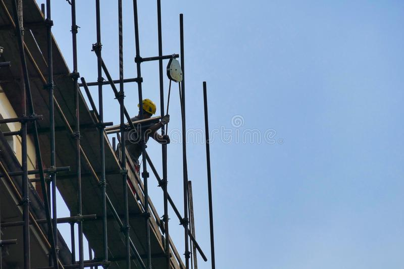 Workers in construction site mounting scaffolding stock images