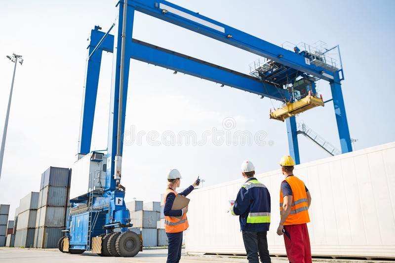 Workers discussing against large crane loading container at shipping yard stock images