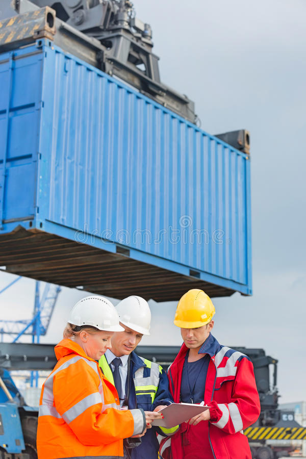 Workers discussing over clipboard in shipping yard stock photo
