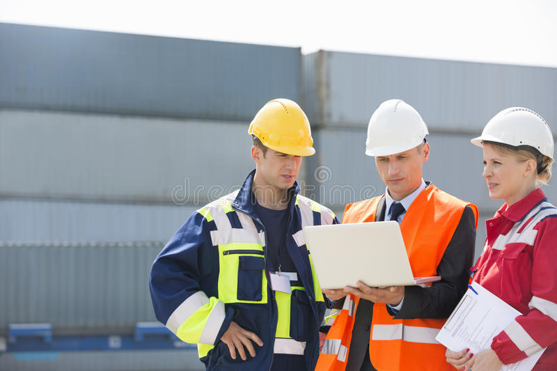 Workers discussing over laptop in shipping yard stock photography