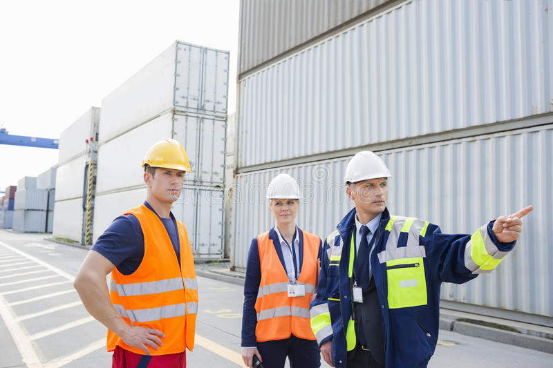Workers discussing in shipping yard royalty free stock image