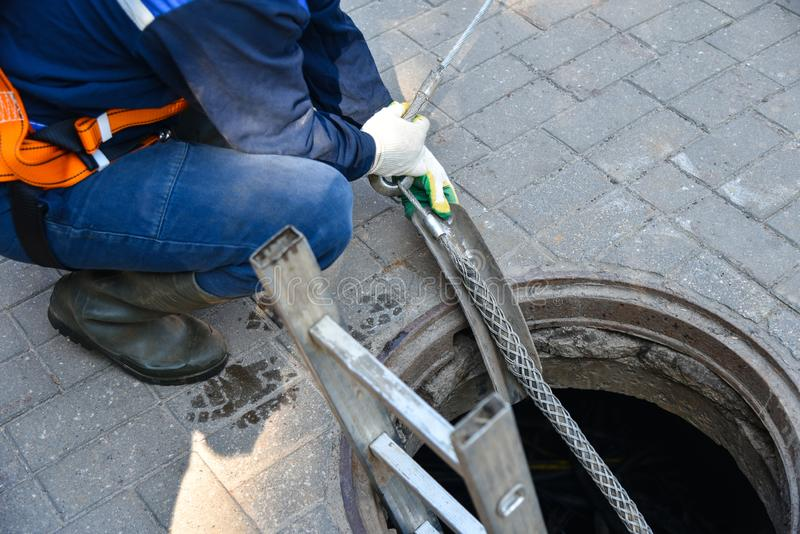 Workers dismantle the telecommunication cable in the well.  royalty free stock image
