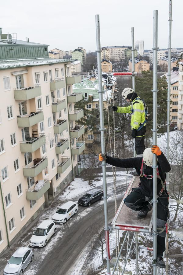 Workers dismantling temporary scaffolding wintertime. Workers dismantling temporary scaffolding after renovation of residential building in Stockholm, Sweden royalty free stock image