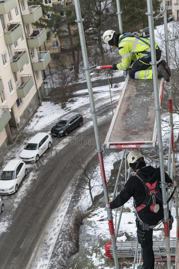 Workers dismantling temporary scaffolding wintertime. Workers dismantling temporary scaffolding after renovation of residential building in Stockholm, Sweden stock images