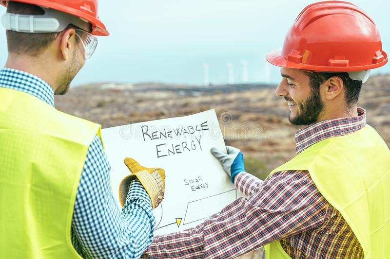 Workers engineers reading and talking about the new renewable energy project - Two builders discussing how to build windmill stock photography