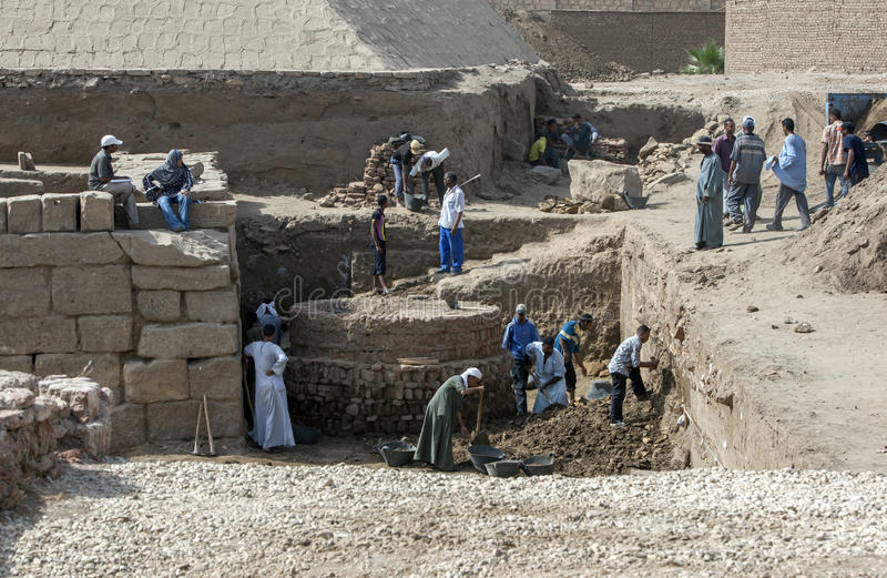 Workers excavate a section of ruins adjacent to the entrance of the Karnak Temple in Luxor, Egypt. The temple complex is dedicated to the Theban gods and to royalty free stock photos