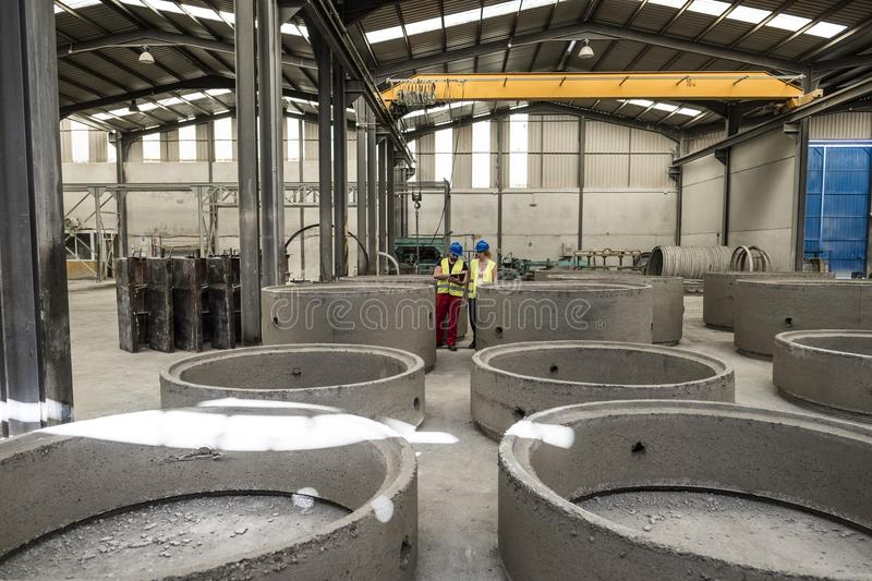 Workers in factory looking concrete structures in factory warehouse. Looking tablet royalty free stock image
