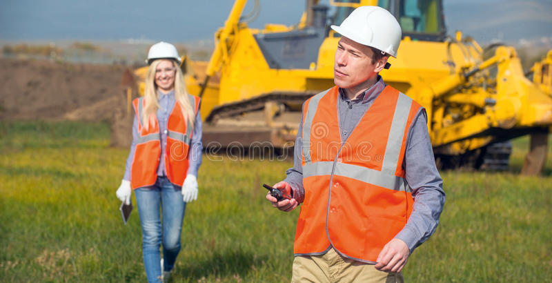 Workers in the field. Construction co-workers discussing about work plan construction site royalty free stock photos