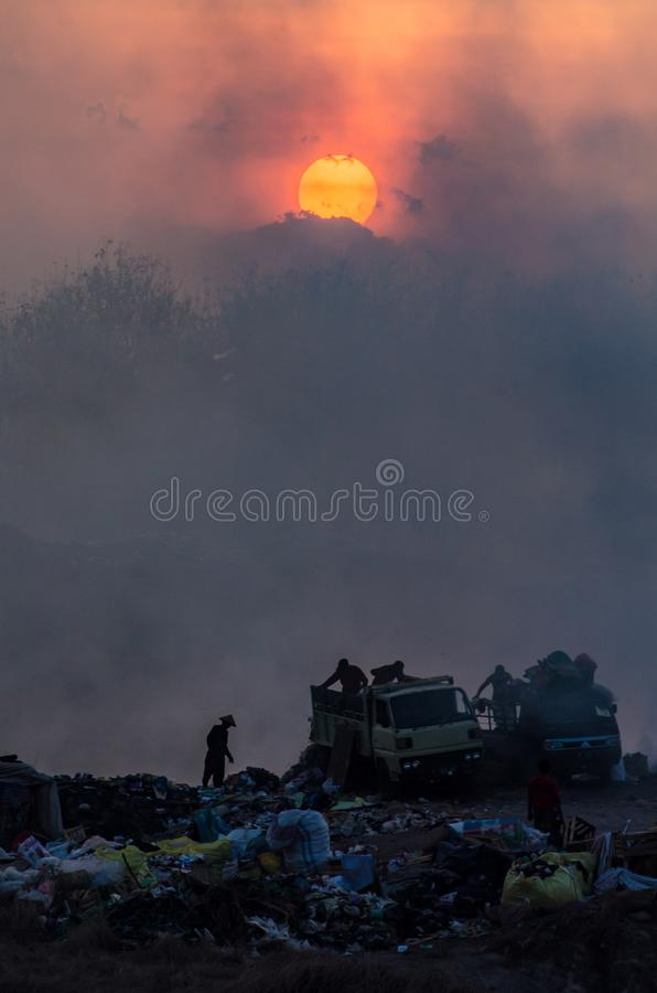 Workers on garbage dump at daybreak royalty free stock photos