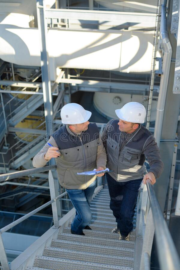 Workers going up stairs in factory royalty free stock images