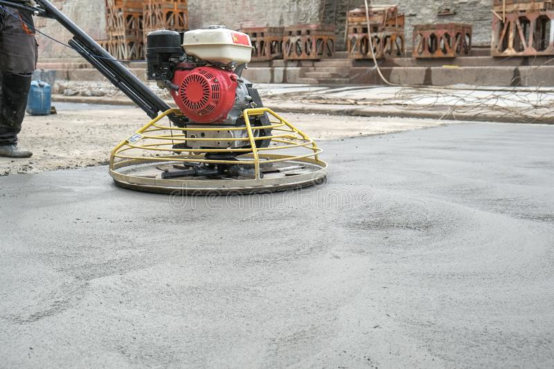 The workers grind the concrete floor at the construction site. Workers grind the concrete floor at the construction site stock photos