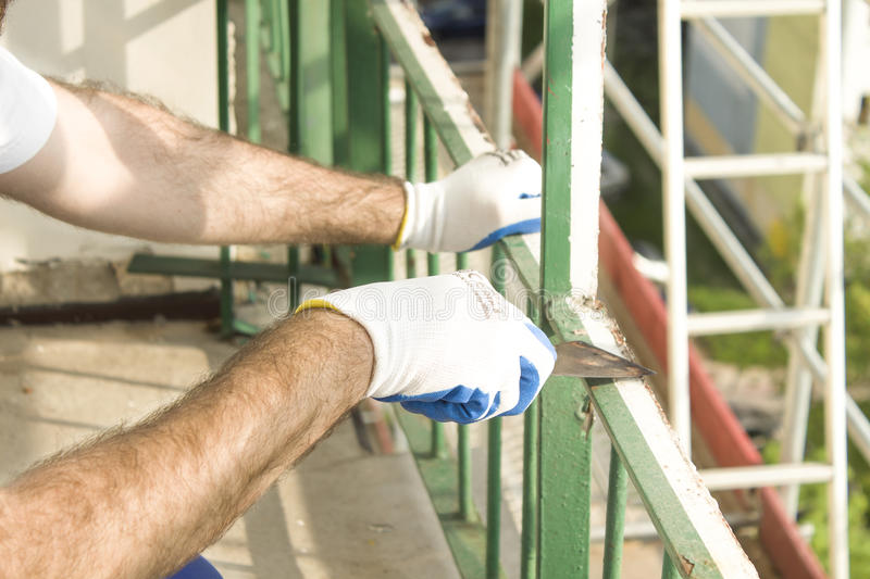Workers` hands in protective gloves remove the old paint from the metal railing with a spatula. Work at high altitude. royalty free stock image