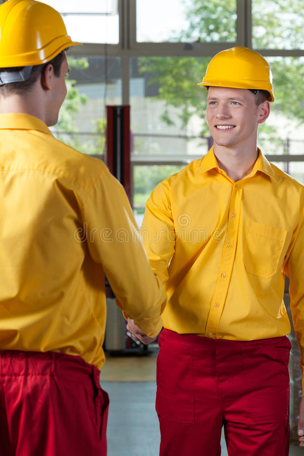 Workers handshake in a factory. View of workers handshake in a factory stock photo
