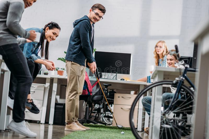 Workers having fun in office man. Workers having fun in office men playing mini golf stock images