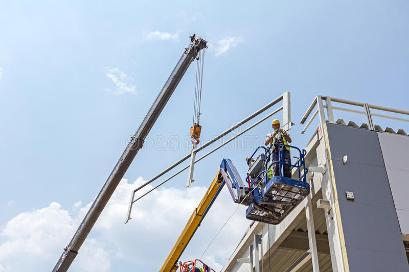 Workers are high up in cherry picker on building site. stock photography