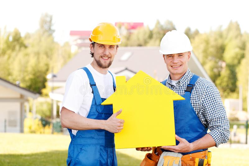 Workers with house model symbol. Construction workers showing house model symbol and friendly smiling royalty free stock images