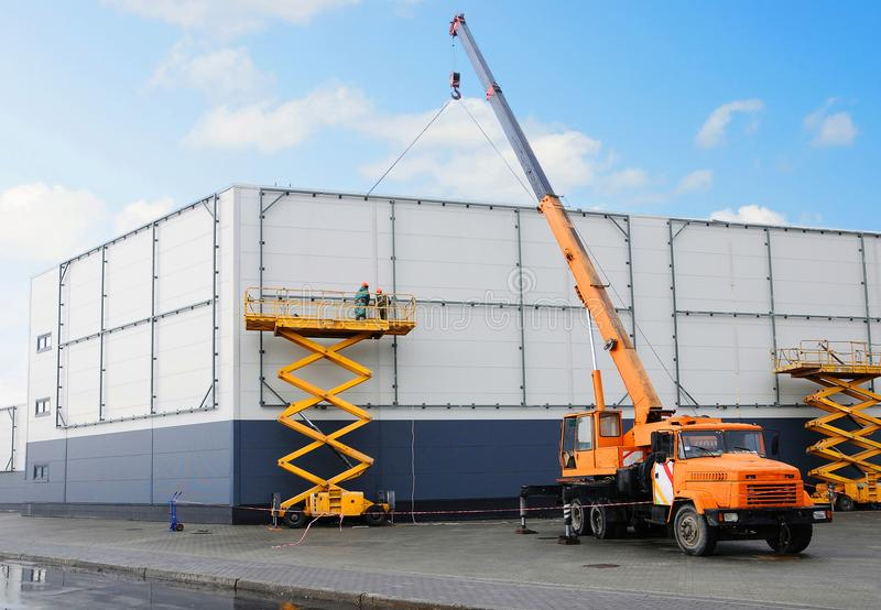 Workers install big billboard on the unfinished building supermarket. Construction crane stock images