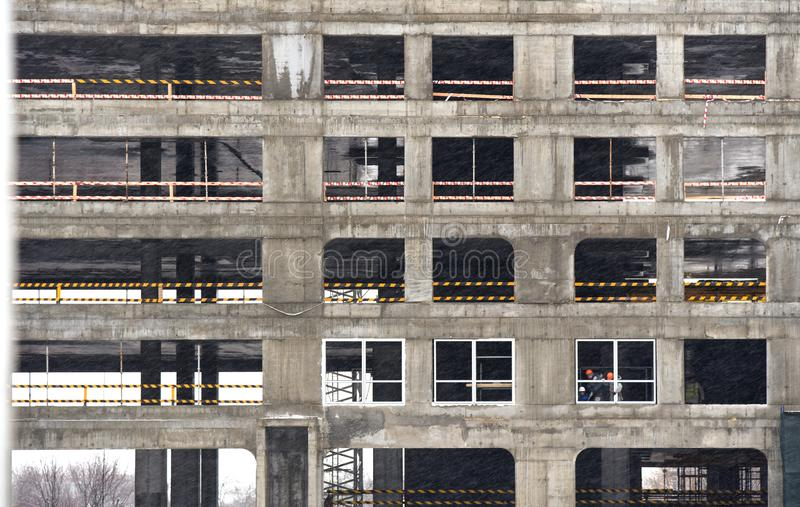 Workers install double-glazed windows in a building under construction. Workers install double-glazed windows in building under construction royalty free stock photo