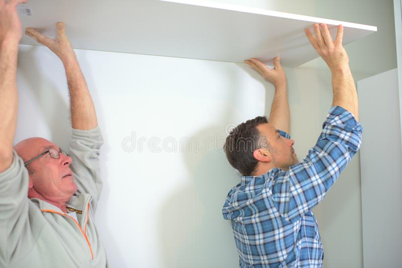 Workers installing ceiling boards building in house construction royalty free stock photography