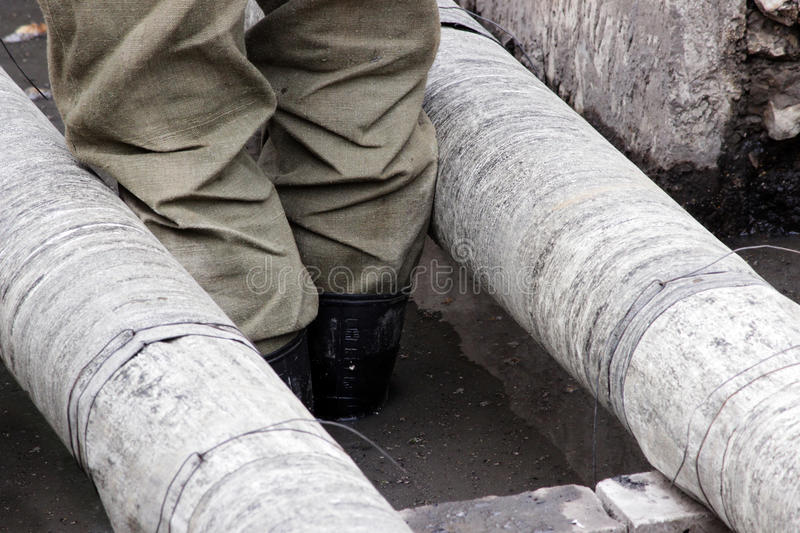 Workers insulate water pipes ruberoid during repair work in a ditch filled. Workers insulate water pipes ruberoid during repair work in a ditch filled with royalty free stock image