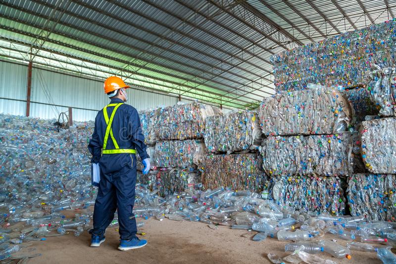Workers in landfill dumping, Garbage engineer, recycling, wearing a safety suit standing in the recycling center have a plastic stock images