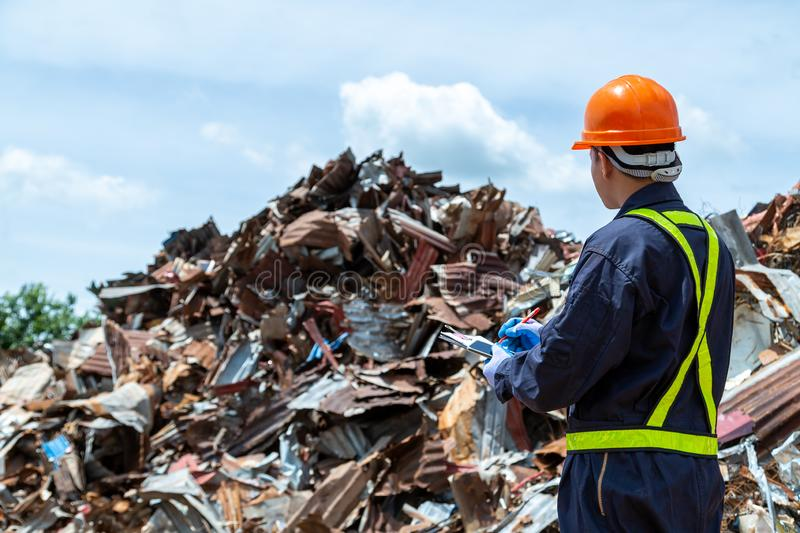 Workers in landfill dumping, Garbage engineer, recycling, wearing a safety suit standing to check the amount of recycled metal royalty free stock photos