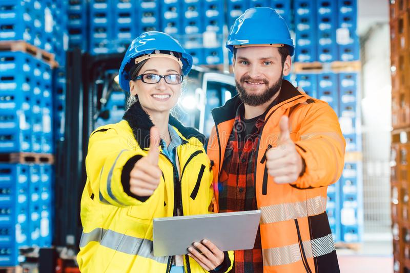 Workers in logistics distribution center showing thumbs-up. After having a success royalty free stock photos