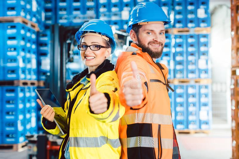Workers in logistics distribution center showing thumbs-up. After having a success stock images