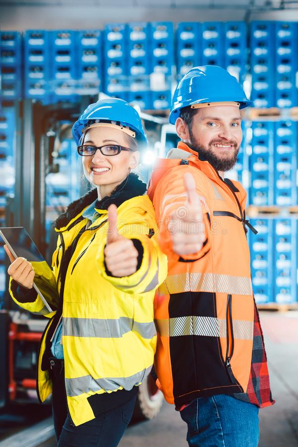 Workers in logistics distribution center showing thumbs-up. After having a success stock photos