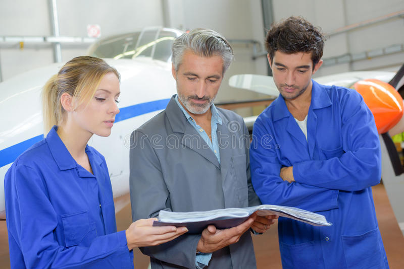 Workers looking at book stood in front aircraft. Workers looking at book, stood in front of aircraft royalty free stock photo