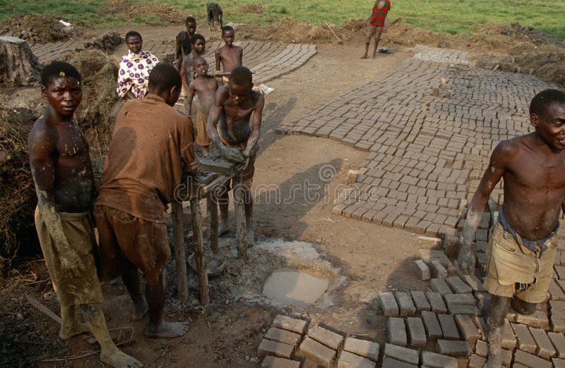 Workers making bricks in Rwanda. They form the clay bricks in moulds then turn them out onto the ground to dry and harden stock photos