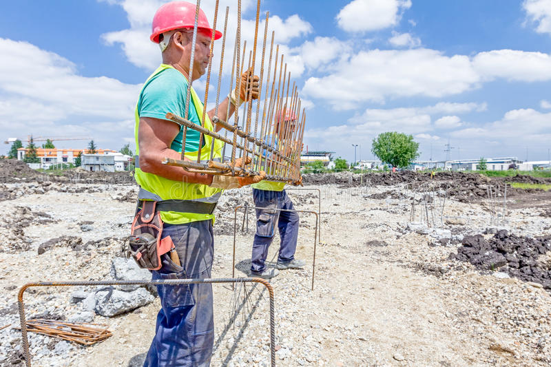 Workers are manually carrying rebar skeleton made for reinforce royalty free stock image