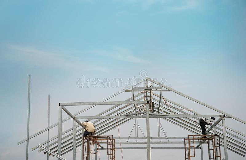 Workers on metal structure home building construction industry w. Workers on metal structure home roof building construction industry with blue sky background stock photos