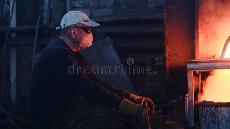 Workers at metallurgical plant working with hot metal. Stock footage. Workers in uniforms and helmets work with. Dangerous hot metal at high temperatures in old stock photo