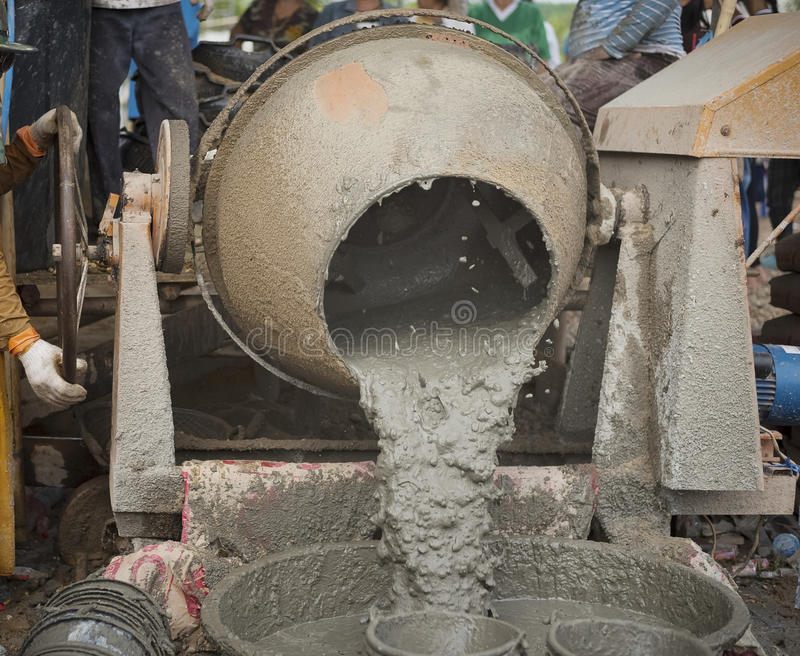 Workers mixing cement. Cement Mixer and the worker royalty free stock image