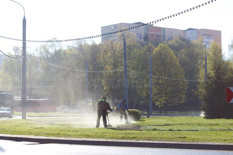 Workers mow grass royalty free stock photos