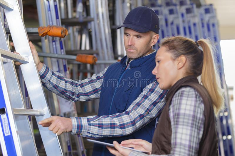 Workers next to aluminum ladder at warehouse royalty free stock photography