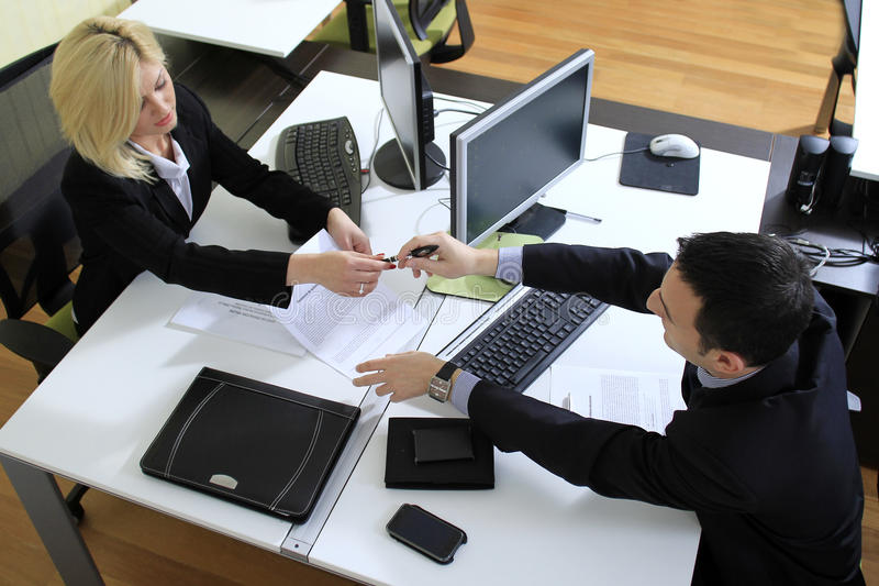 Workers in office. Overhead view of young man and woman coworkers passing pen over office desk with keyboards and computer screens