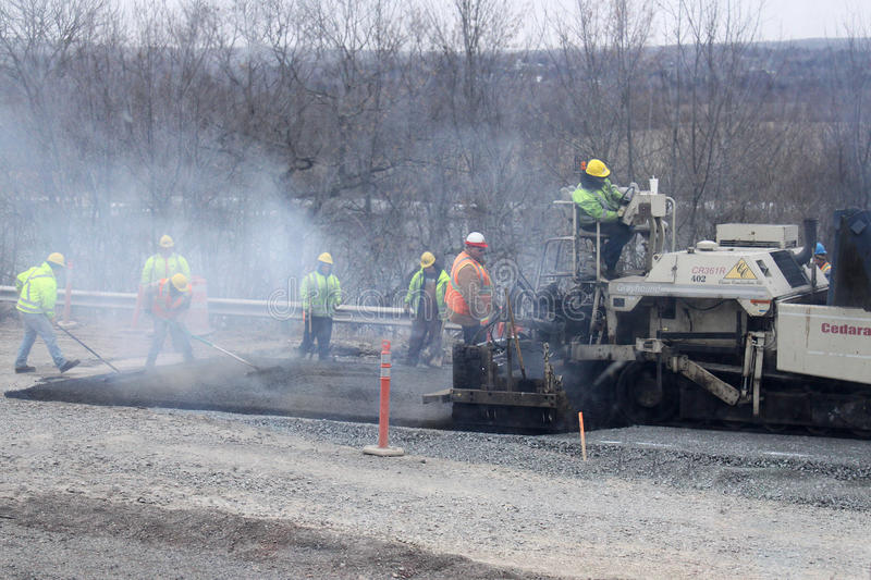 Workers paving a road royalty free stock photography