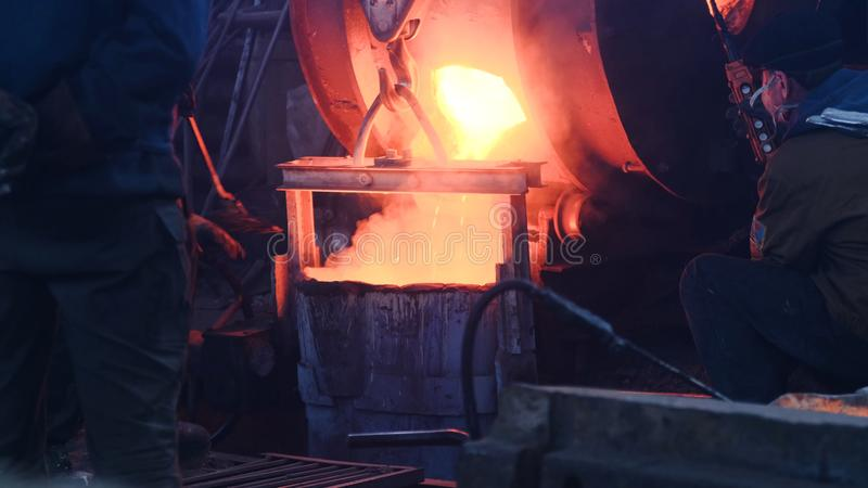 Workers poured molten metal at plant. Stock footage. Workers in form and helmets control process of pouring molten metal. From boiler at metallurgical plant royalty free stock photo