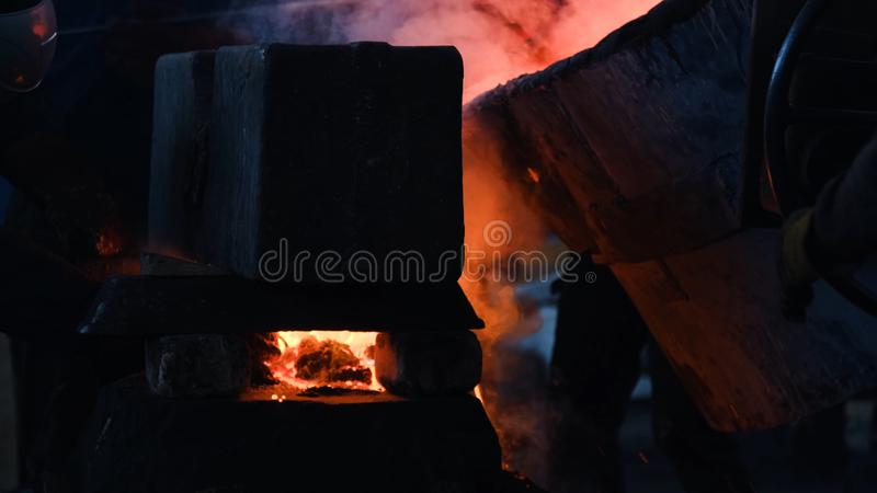 Workers poured molten metal at plant. Stock footage. Workers in form and helmets control process of pouring molten metal. From boiler at metallurgical plant stock images