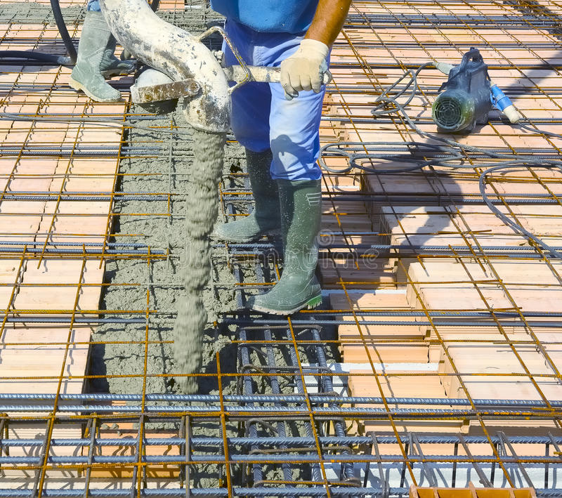 Workers pouring concrete on big floor construction. On the construction site, with motion blur stock images