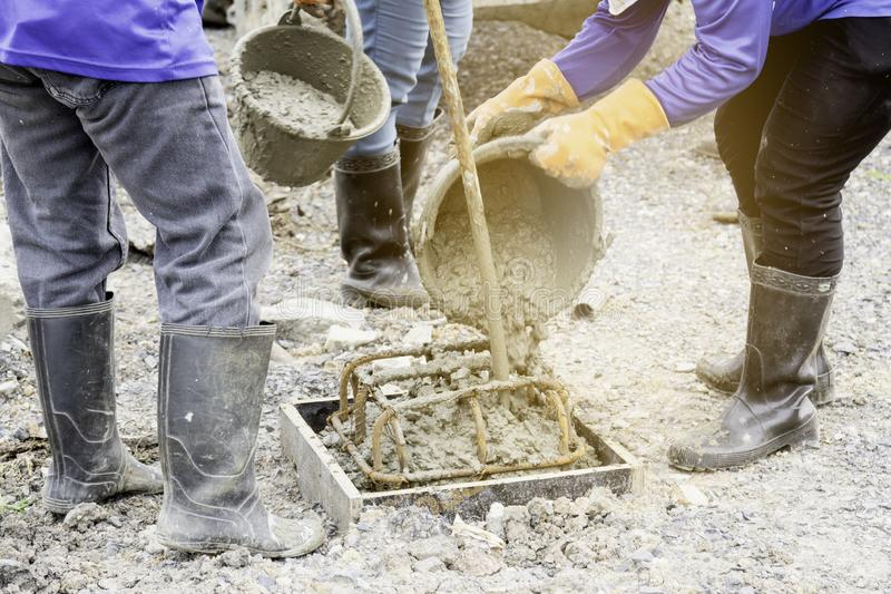 Workers are pouring concrete out of the tank to make a pile casting.  stock photos