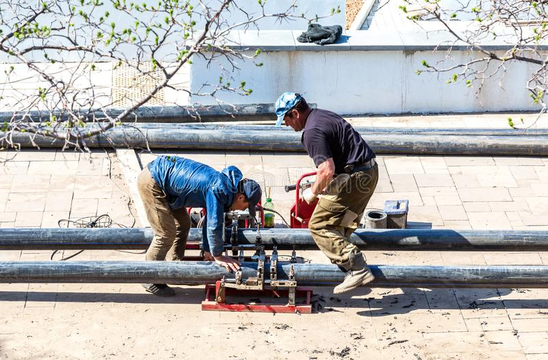 Workers produce work of laying plastic pipes stock photo