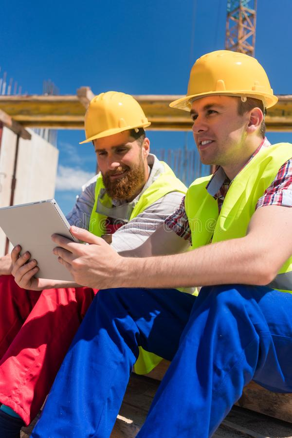 Workers reading or watching a video on a tablet PC during break at work stock photo