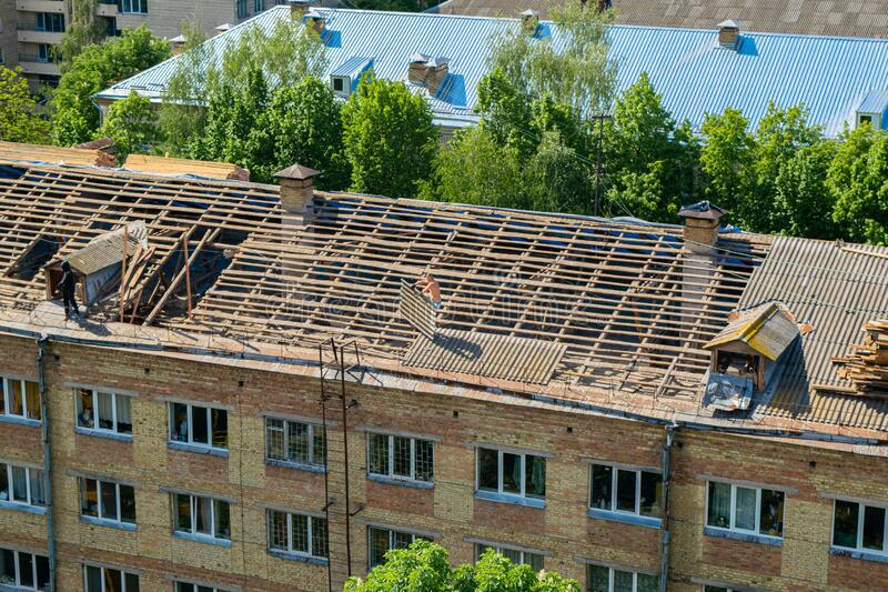 Workers repair and replace roofing on an old red brick building. Spring construction work. Repair and maintenance of city royalty free stock image