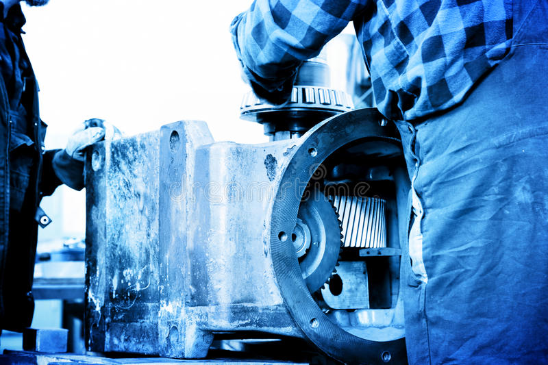 Workers repair, work on old gear element in workshop. Industry royalty free stock images