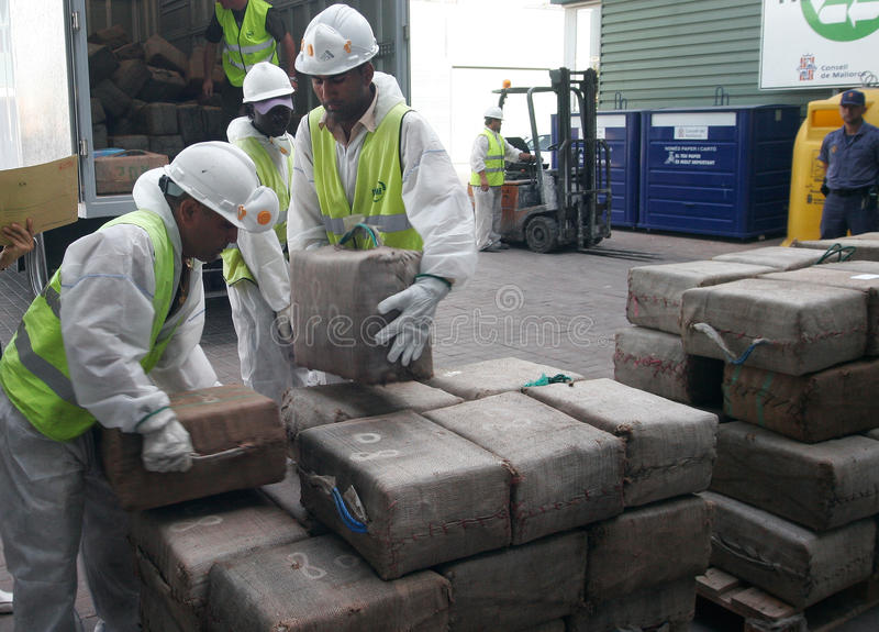 Workers retrieve drug packs from a truck before its destruction. Police workers retrieve packs of drugs from a truck to proceed to its incineration after the stock photos